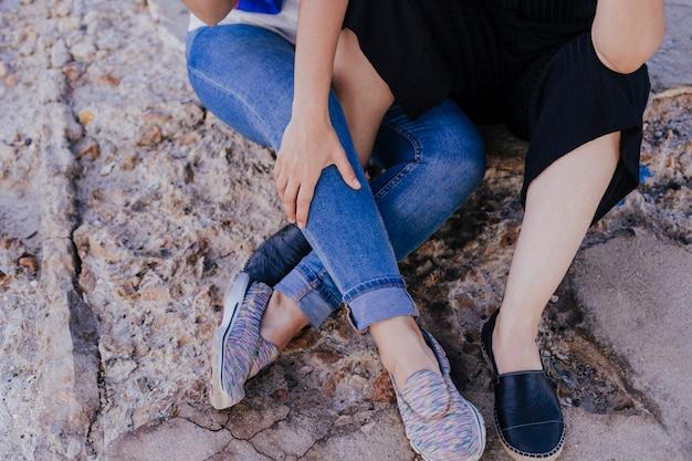 Młoda nierozpoznawalna para lesbijek siedzi na zewnątrz
