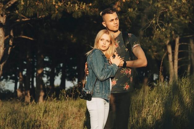 Młoda niesamowita para przytulająca się podczas podróży na zewnątrz w czasie wakacji, gdzie dziewczyna opiera głowę na piersi swojego chłopaka, podczas gdy on patrzy w inną.