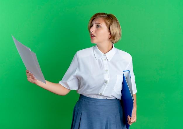Młoda niespokojna blondynka rosjanka trzyma arkusz papieru i folder patrząc na bok na białym tle na zielonym tle z miejsca na kopię