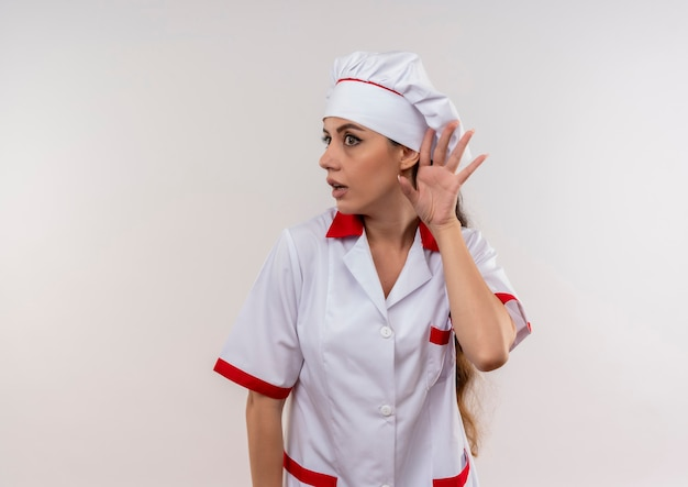 Młoda niespokojna dziewczynka kaukaski kucharz w gestach munduru szefa kuchni nie słyszy na białym tle z miejsca na kopię