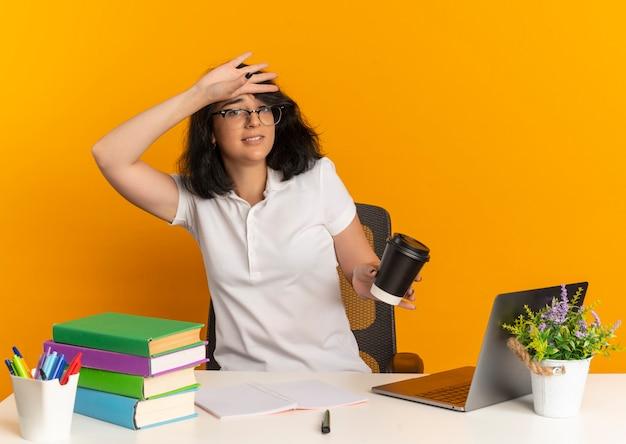 Młoda niespokojna ładna kaukaska uczennica w okularach siedzi przy biurku ze szkolnymi narzędziami kładzie rękę na czole trzymając filiżankę kawy na pomarańczowo z miejscem na kopię