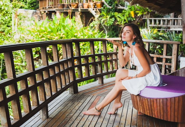 Młoda, niewinna, czysta piękna kobieta śni, siedzi na kanapie w białej sukni, romantyczny, liryczny, myślący, zielona tropikalna przyroda, lato, zrelaksowany, chłód, nogi, hotel wypoczynkowy