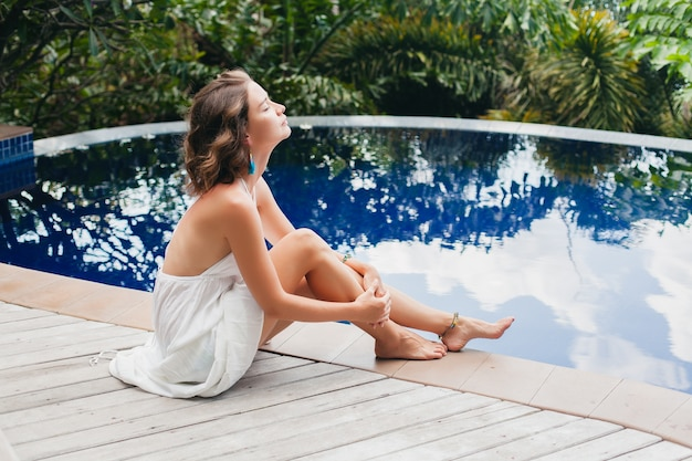 Młoda niewinna czysta piękna kobieta śni, siedzi przy basenie w białej sukience, romantyczna, liryczna, myśląca, zielona tropikalna przyroda, lato, zrelaksowana, chłód, długie nogi