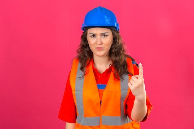 Młoda niezadowolona kobieta budowniczy w mundurze budowlanym i kasku ochronnym skierowana w górę z ostrzeżeniem palcem wskazującym na izolowanym różowym tle