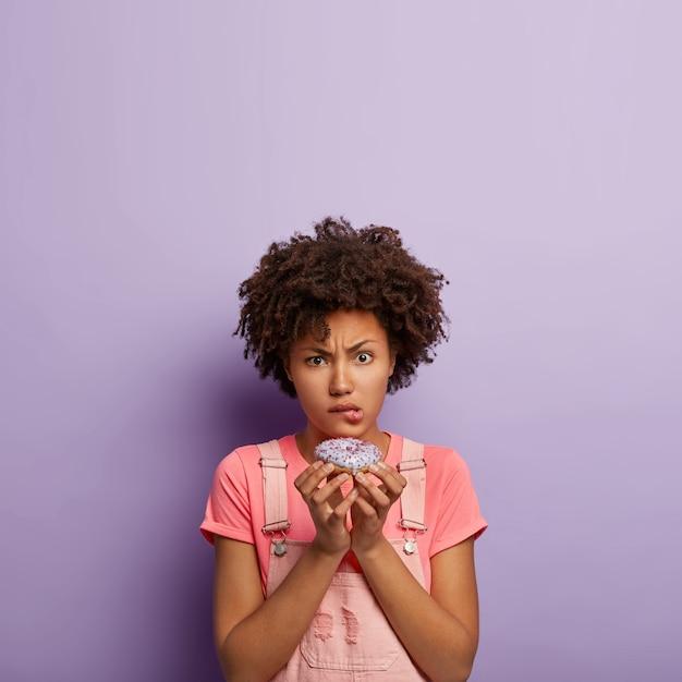 Młoda niezadowolona kobieta trzyma pysznego słodkiego pączka
