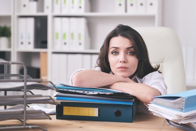 Młoda niezadowolona księgowa lub sekretarka leży na grubym stosie dokumentów finansowych, siedząc przy biurku przed kamerą