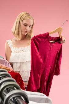 Młoda niezadowolona ładna dziewczyna patrzy na sukienki i przymierza je, wybierając w sklepie