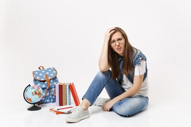 Młoda niezadowolona zdenerwowana studentka w dżinsowych ubraniach przylegająca do głowy siedzącej w pobliżu kuli ziemskiej, plecaka, podręczników szkolnych na białym tle