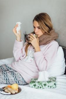 Młoda niezdrowa kobieta z herbatą na rękach źle się czuje