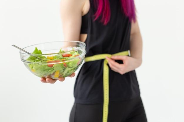 Młoda niezidentyfikowana atletka o fioletowych włosach mierzy miarkę w talii i trzyma sałatkę warzywną. pojęcie prawidłowego odżywiania i dobrej kondycji.