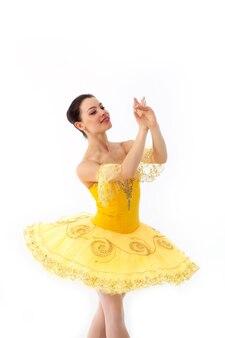 Młoda nowoczesna balerina z żółtą tutu robi pozę.