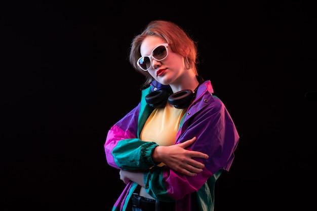 Młoda, nowoczesna dama z przodu, w kolorowym pomarańczowym płaszczu z czarnymi słuchawkami i okularami przeciwsłonecznymi, pozuje do tańca nowoczesnej mody
