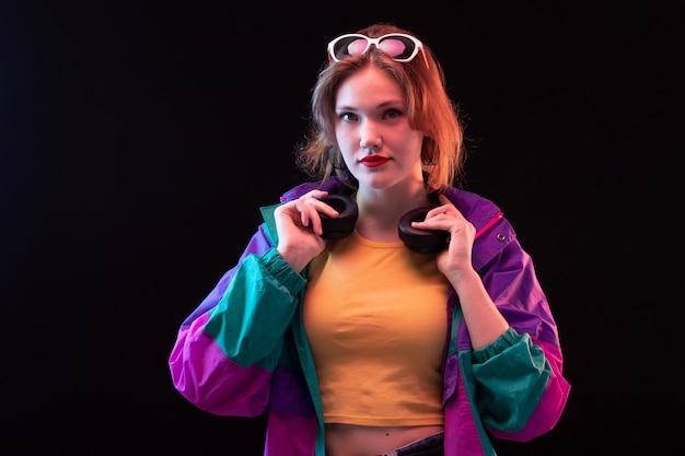 Młoda, nowoczesna dama z przodu w kolorowym pomarańczowym płaszczu z czarnymi słuchawkami i okularami przeciwsłonecznymi