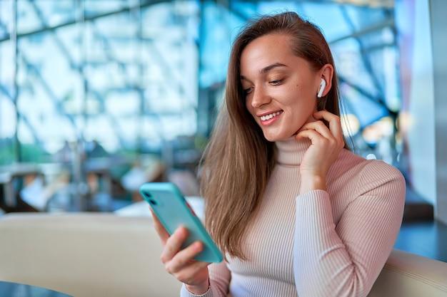Młoda nowoczesna dorywczo szczęśliwa radosna kobieta nosi słuchawki bezprzewodowe za pomocą smartfona do oglądania wideo i czytania wiadomości online, siedząc i odpoczywając w kawiarni
