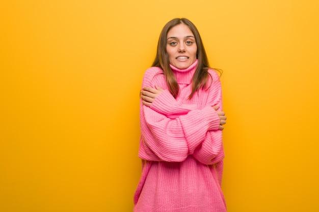 Młoda nowoczesna kobieta ma zimno z powodu niskiej temperatury