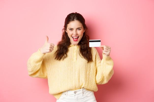 Młoda nowoczesna kobieta mówi tak i pokazuje kciuk do góry, trzymając plastikową kartę kredytową, stojąc nad różową ścianą. skopiuj miejsce
