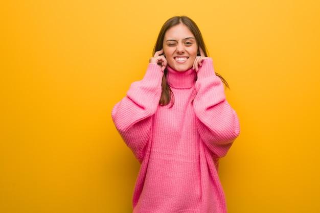 Młoda nowoczesna kobieta obejmujące uszy rękami