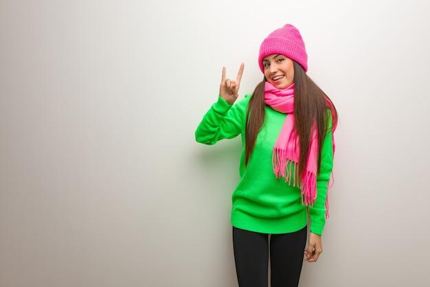 Młoda nowoczesna kobieta robi rockowy gest
