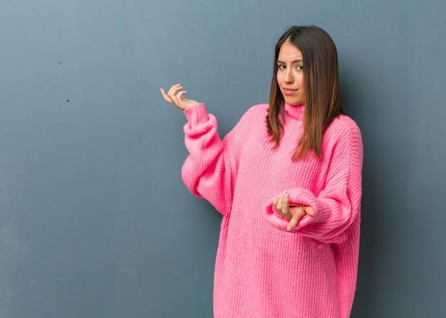 Młoda nowoczesna kobieta zmieszana i wątpliwa
