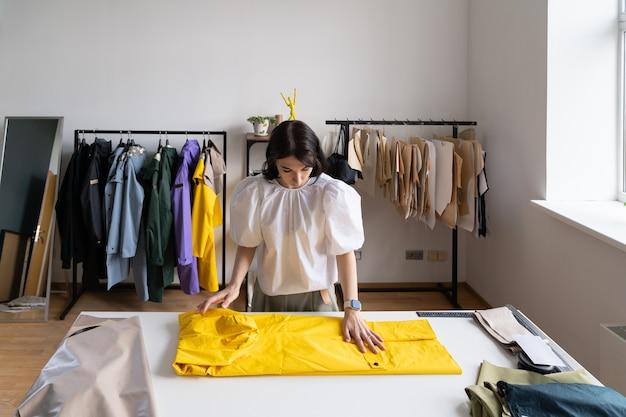 Młoda nowoczesna krawcowa dziewczyna pracuje na ubraniach w modnej kolekcji płaszczy przeciwdeszczowych w studio atelier