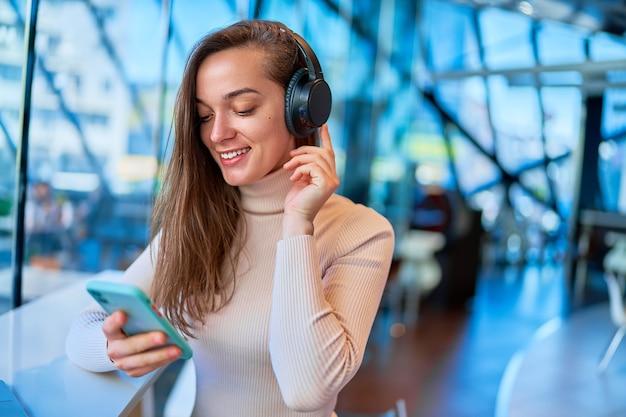 Młoda nowoczesna szczęśliwa radosna kobieta sobie słuchawki bezprzewodowe za pomocą smartfona do oglądania wideo online, siedząc w kawiarni
