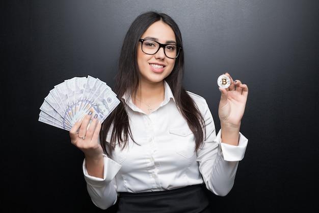 Młoda nowoczesna udana biznesowa kobieta w okularach trzyma pieniądze bitcoin i gotówkę na białym tle na czarnej ścianie