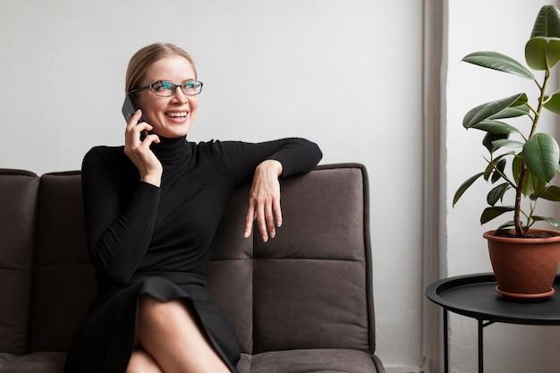 Młoda nowożytna kobieta opowiada przy telefonem