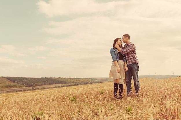 Młoda nowożytna stylowa para outdoors. romantyczna młoda para zakochanych na zewnątrz na wsi