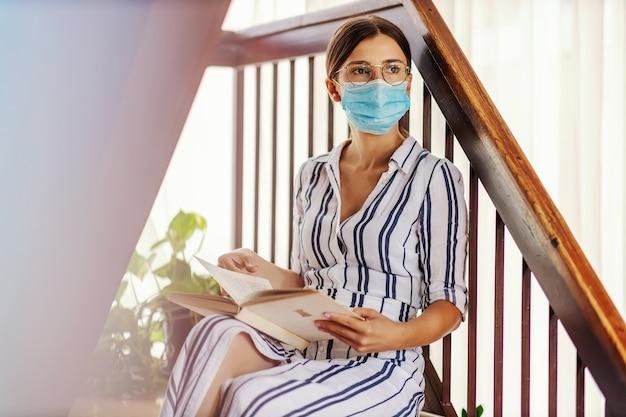 Młoda oddana inteligentna studentka z maską na twarzy siedząca na schodach i czytająca książkę podczas pandemii wirusa koronowego.