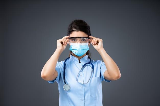Młoda oddana lekarzowi kobieta z maską ochronną zakładającą okulary ochronne.