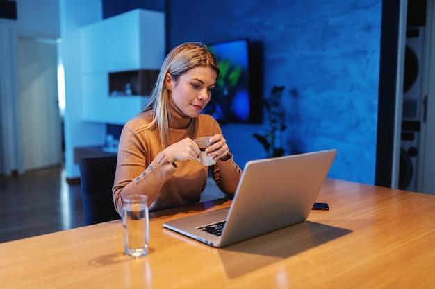 Młoda oddana, oszałamiająca blond przedsiębiorczyni siedzi w domu, pije kawę i pracuje nad ważnym projektem