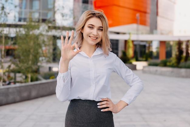 Młoda, odnosząca sukcesy kobieta biznesu obok nowoczesnych wielokondygnacyjnych budynków biurowych czerwony biurowiec
