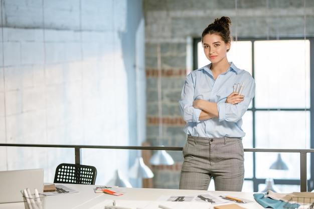 Młoda odnosząca sukcesy projektantka mody skrzyżowana ramionami przy klatce piersiowej, stojąc przed kamerą w studio