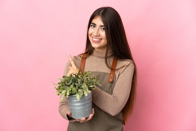 Młoda ogrodniczka dziewczyna trzyma roślinę na białym tle