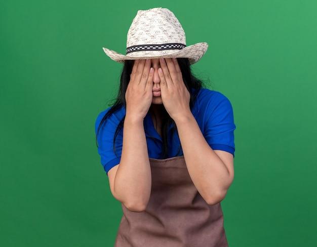 Młoda ogrodniczka dziewczyna ubrana w mundur i kapelusz zakrywający twarz rękami odizolowanymi na zielonej ścianie z miejscem na kopię