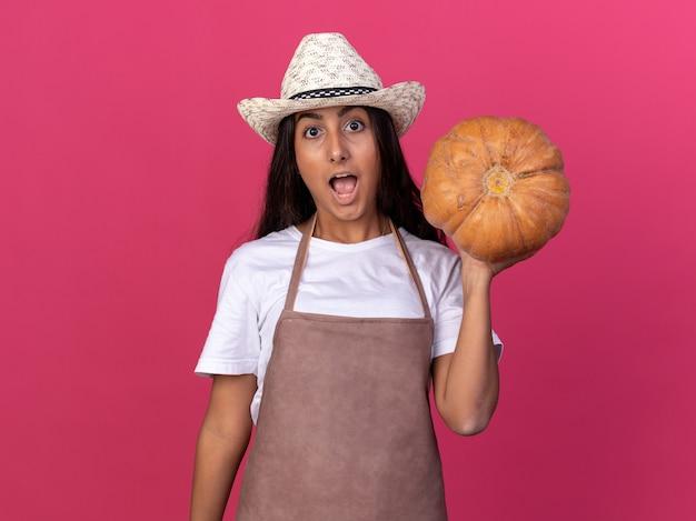 Młoda ogrodniczka dziewczyna w fartuch i letni kapelusz trzyma dyni zaskoczony i zdumiony stojąc nad różową ścianą
