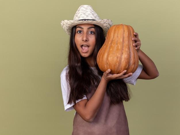 Młoda ogrodniczka dziewczyna w fartuch i letni kapelusz trzyma dyni zdumiony i zaskoczony stojąc nad zieloną ścianą