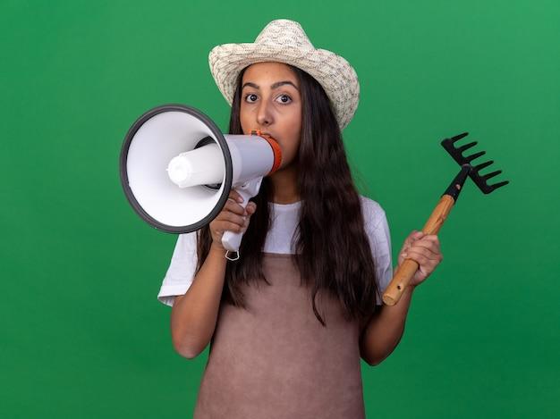 Młoda ogrodniczka dziewczyna w fartuch i letni kapelusz trzyma mini prowizji krzycząc do megafonu stojącego nad zieloną ścianą