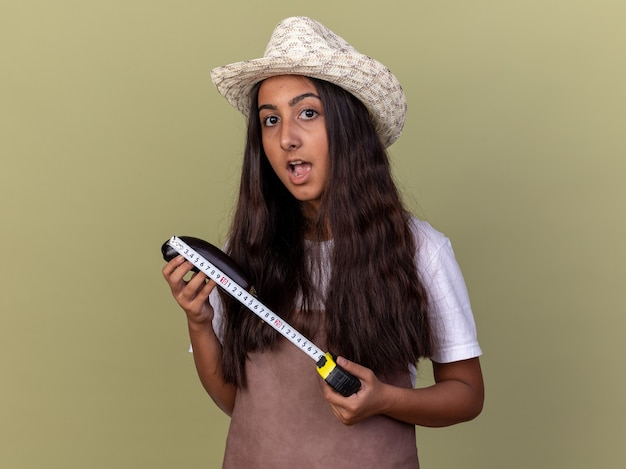 Młoda ogrodniczka dziewczyna w fartuch i letni kapelusz trzymając miarkę szczęśliwa i zaskoczona stojąc nad zieloną ścianą