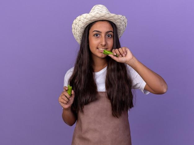 Młoda ogrodniczka dziewczyna w fartuch i letni kapelusz trzymając zieloną paprykę chili będzie go gryźć uśmiechnięty zdezorientowany stojąc nad fioletową ścianą