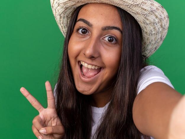 Młoda ogrodniczka dziewczyna w fartuch i letni kapelusz uśmiecha się radośnie pokazując znak v stojący nad zieloną ścianą