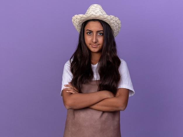 Młoda ogrodniczka dziewczyna w fartuch i letni kapelusz z poważną twarzą z rękami skrzyżowanymi stojąc na fioletowej ścianie