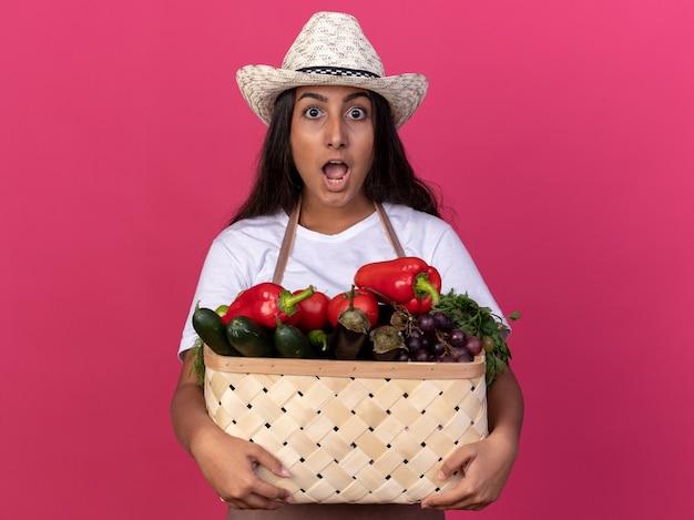 Młoda ogrodniczka dziewczyna w fartuchu i letnim kapeluszu trzyma skrzynię pełną warzyw zaskoczona i zdumiona stojąc nad różową ścianą