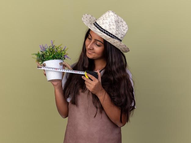 Młoda ogrodniczka dziewczyna w fartuchu i letnim kapeluszu trzyma taśmę mierniczą i roślinę doniczkową patrząc na roślinę z uśmiechem na twarzy stojącej nad zieloną ścianą