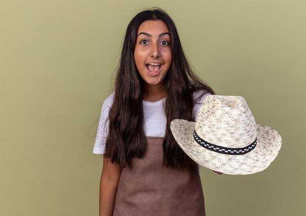 Młoda ogrodniczka dziewczyna w fartuchu pokazuje jej letni kapelusz szczęśliwy i zaskoczony uśmiechnięty stojący nad zieloną ścianą