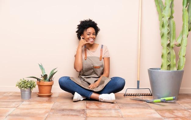 Młoda ogrodniczka kobieta siedzi na podłodze