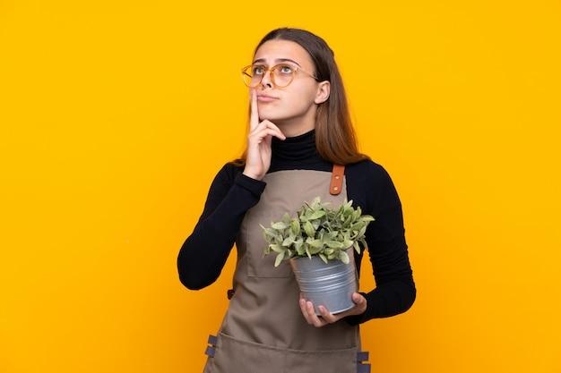 Młoda ogrodniczka kobieta trzyma rośliny nad odosobnioną kolor żółty ścianą myśleć pomysł
