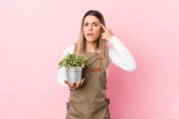 Młoda ogrodniczka kobieta trzyma rośliny pokazuje rozczarowanie gest z palcem wskazującym.
