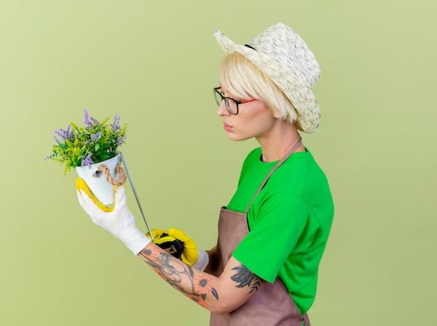 Młoda ogrodniczka kobieta z krótkimi włosami w fartuch i kapelusz trzymając roślinę doniczkową mierząc ją taśmą mierniczą patrząc pewnie stojąc na jasnym tle