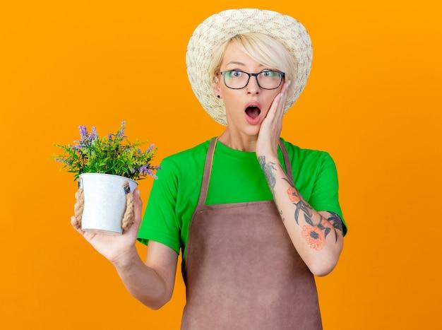 Młoda ogrodniczka kobieta z krótkimi włosami w fartuchu i kapeluszu trzymająca doniczkową roślinę patrząc na kamerę, która jest zaskoczona i zdumiona stojąc na pomarańczowym tle